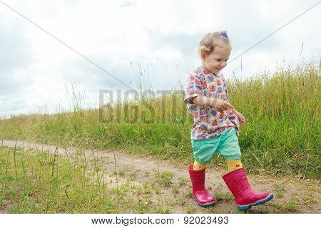 Two Years Old Preschooler Girl Walking By Foot On Farm Field Summer Dirt Road