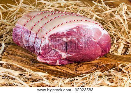 British Boneless Pork Shoulder on cutting board and straw