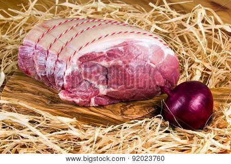 Farm British Boneless Pork Shoulder on cutting board and straw, onion