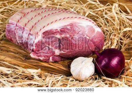 Farm British Boneless Pork Shoulder on cutting board and straw, onion, garlic