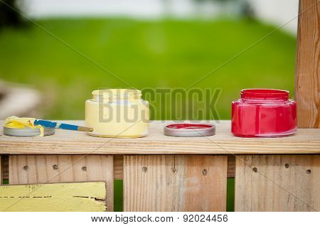 Open Paint Containers On A Wooden Booth