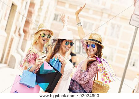 A picture of a group of happy friends shopping in the city