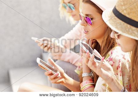 A picture of group of friends using smartphones in the city