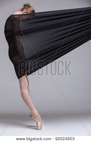 Slim dancer plays with black mesh fabric