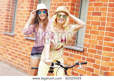 A picture of two girl friends riding a tandem bicycle in the city