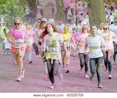 Group Of Young Girls Covered With Color Powder Running