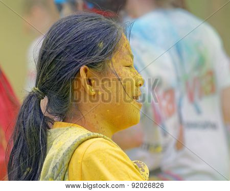 Face Of Asian Woman Covered With Yellow Color Powder