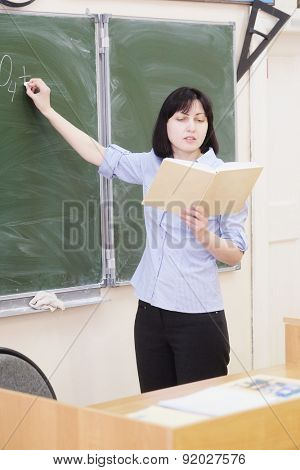 The girl teacher stands at a blackboard