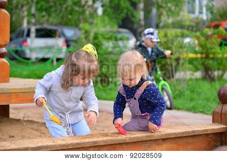 Two Little Sisters Playing In  Sandbox