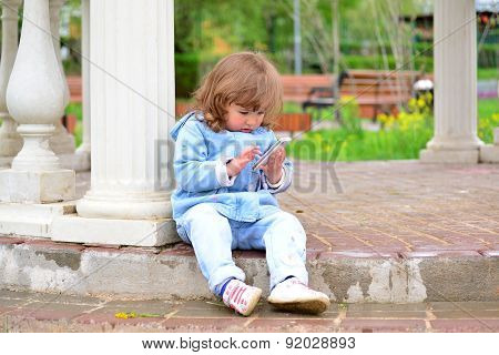 Girl Two Years, With A Cell Phone In The Park