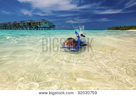 Young boy swimming and snorkeling in shallow tropical lagoon