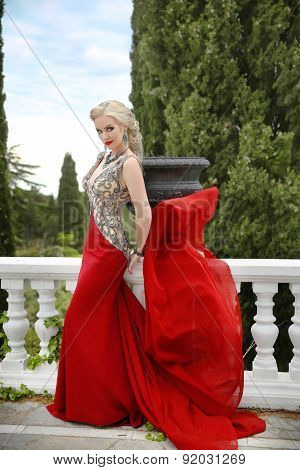 Woman In Red Waving Dress. Fashion Blond Model In Blowing Gown On Balcony With White Baluster. Outdo