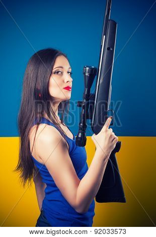 Beautiful Young Woman Posing With Rifle Against Blue And Yellow Background