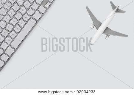 High angle shot of a keyboard and jet plane representing 'online airfare booking' concept. All objects are white and silver. Horizontal format with copy space.