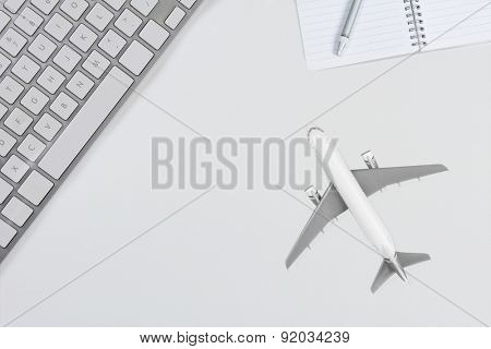 Aerial photo of a keyboard, notepad and jet plane representing 'online airfare booking' concept. All objects are white and silver. Horizontal format with copy space.
