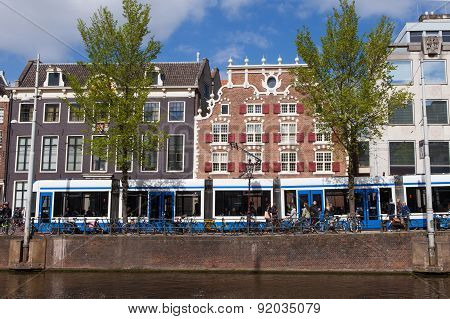 Amsterdam, The Netherlands - May 15, 2015: Tram (Local light rail transportation) heading to Amsterdam central station with the Church of Saint Nicolas in the background.