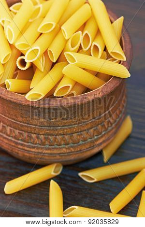 Pasta in wooden bowl, on wood background