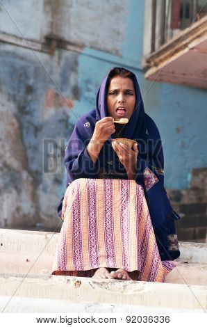 Indian Woman Eating A Meal On The Ghat Near Sacred River Ganges In Varanasi