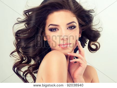 Beautiful girl model with long brown curled hair