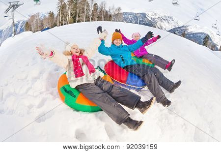 Group of children with arms up slide on tubes