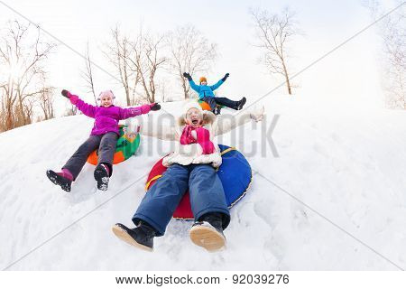 Excited group of children sliding down on tubes