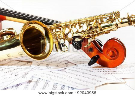Cello tuning pegs and shiny golden alto saxophone