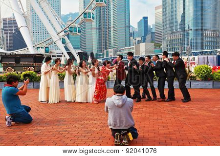 HONG KONG, DECEMBER 11, 2014: Hong Kong Special Administrative Region. Youth wedding photographed in a public park near the ferris wheel.  The modern city on the ocean coast