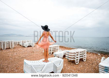 Woman on the deserted beach with many sunbeds