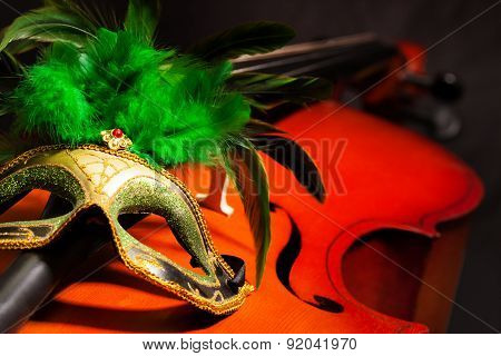 Close-up of Venetian mask with feathers on cello