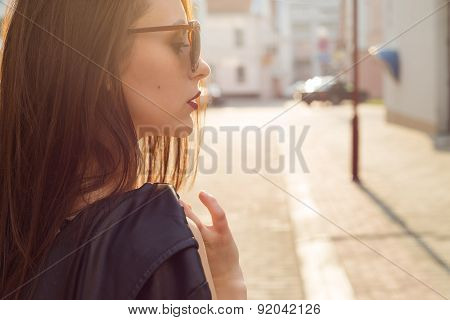 beautiful stylish girl in a black leather jacket with sun glasses with a dark lipstick in the city