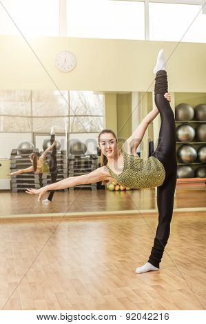 Young Woman Doing Standing Split In Fitness Class