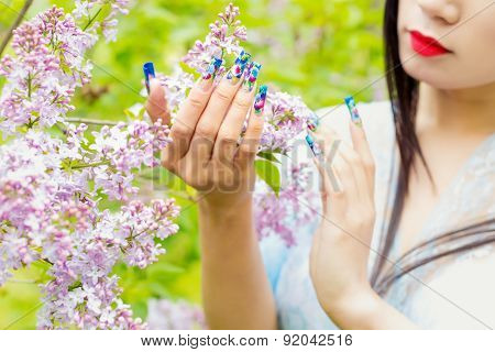 beautiful hands girls with fake long nails with pictures holding a branch of lilac in the garden