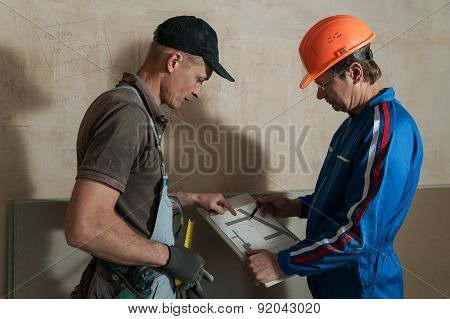 Worker And Foreman Discuss The Scheme Plasterboard Ceiling