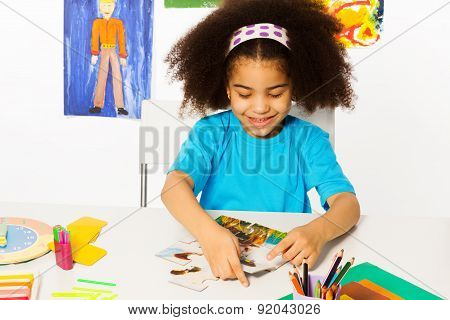 Small African girl putting puzzle pieces together