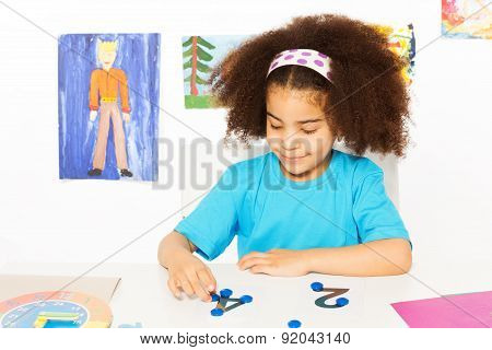 Girl puts blue coins learning to count