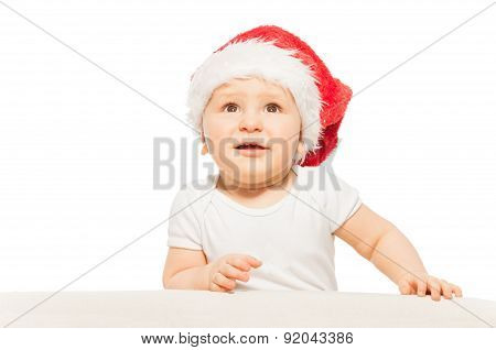 Baby in red Xmas hat looks up on white background