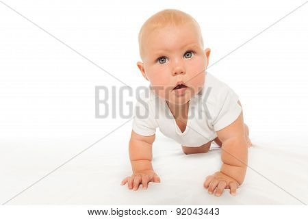 Curious looking baby crawls wearing white bodysuit