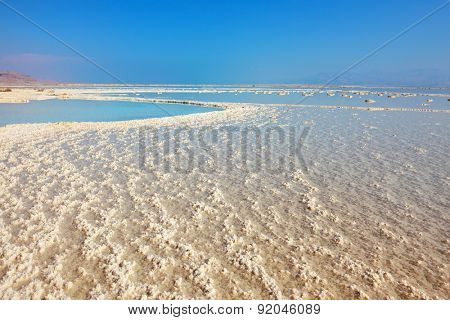 The shoaled Dead Sea at coast of Israel. The condensed salt out over a water surface