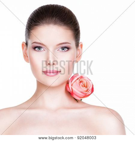 Portrait of pretty face of beautiful woman with a pink rose - isolated on white.