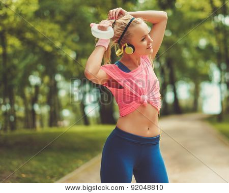 Sporty woman in a park with drinking bottle