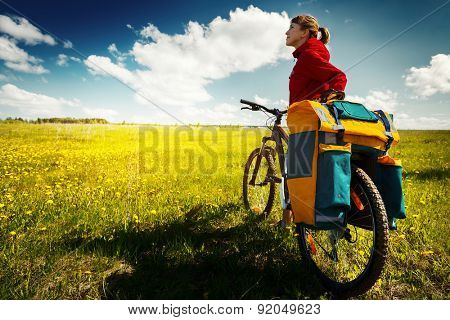 Woman with loaded bicycle on the green meadow with flowers at sunny day