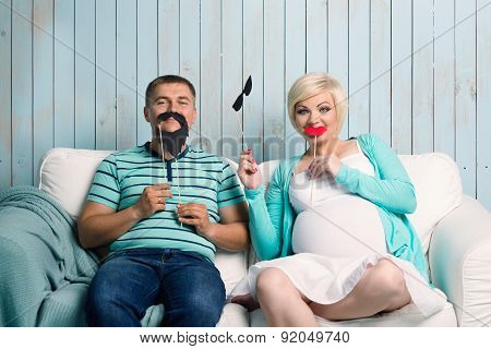 Pregnant couple with false mustaches
