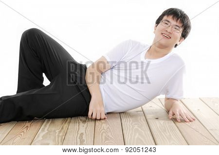 Young Asian man lying on wooden floor isolated