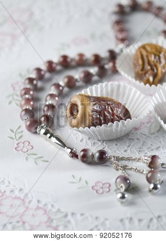 Arabic dates arranged in white paper cups with islamic prayer beads. Ramadan objects.