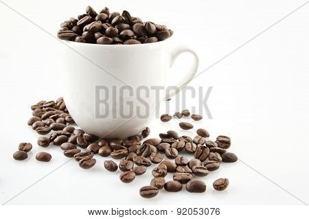 Coffee Cup Full Of Coffee Beans On White
