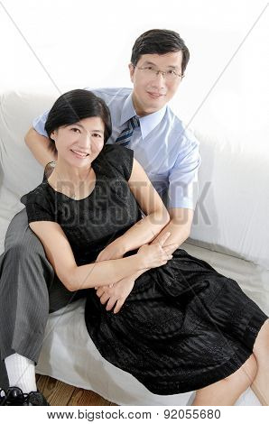 Portrait shot of an attractive, successful and happy middle aged man and woman sitting together at home on a sofa, smiling and laughing