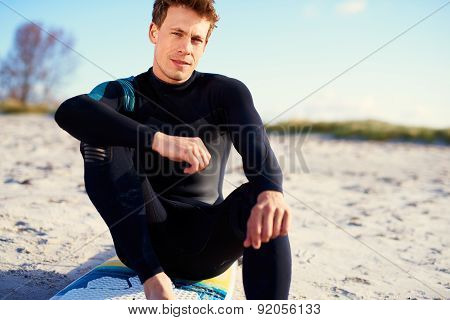 Serious Young Man Sitting On His Surfboard