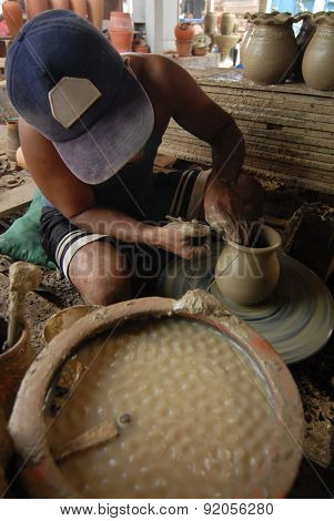 Young potter creating a clay pot on a Potters wheel