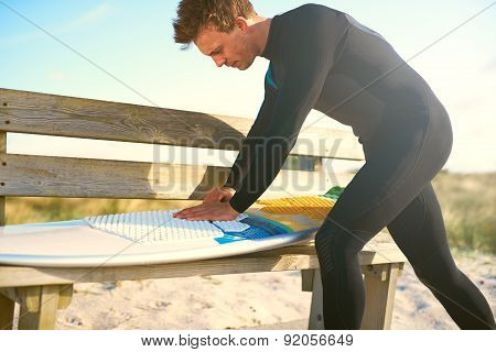 Male Surfer Waxing His Surfboard On The Bench