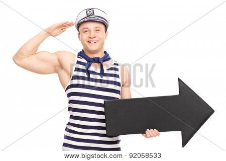 Young male sailor saluting towards the camera and holding a big black arrow pointing right isolated on white background